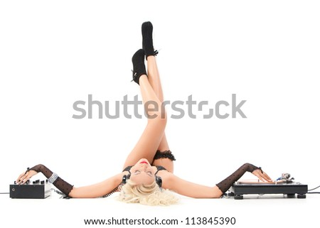 sexy woman in headphones lying with dj equipment and her legs on the white wall