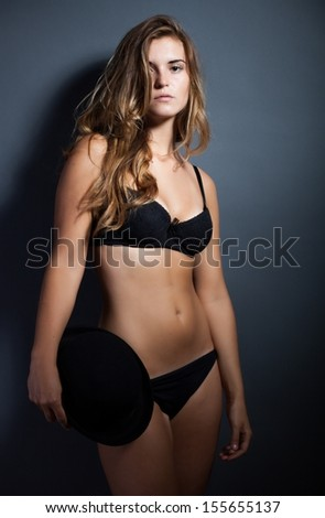 Sexy woman in lingerie and hat on dark background