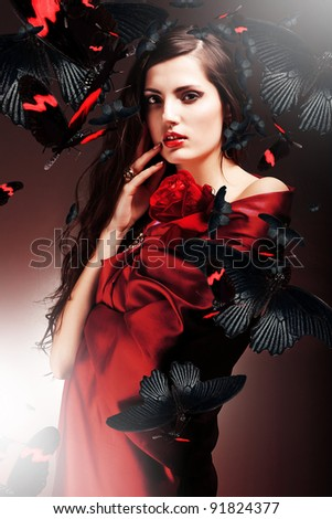 sexy woman in red fabric with red rose and butterflies