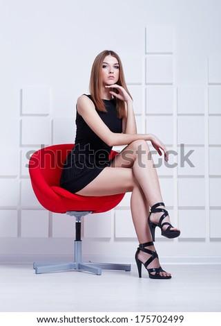 Sexy woman in short black dress sitting on a chair. Fashion shot