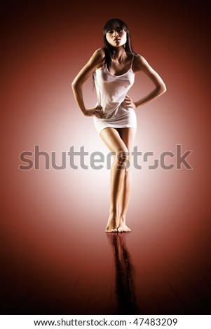 Sexy woman in tight summer dress on studio background