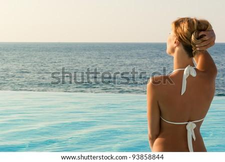 Sexy woman in white bikini near edge of infinity pool looking far on horizon. Crete. Greece