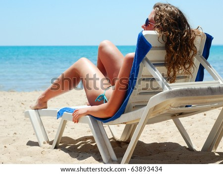 sexy woman is lying on beach bed near a sea, view from behind