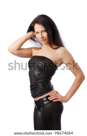 Sexy woman is standing sideways and looking at the camera. Other hand is in her hair, another on her hip. Pretty girl is wearing a black leather top and tight pants. - stock photo