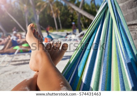 Sexy woman legs in hammock on beach. Vacation concept