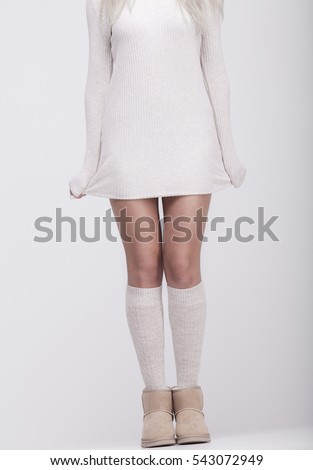 Sexy woman legs in socks and uggs on grey background.