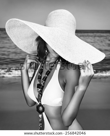 Sexy woman on the beach, black and white photo of fashion model posing on seashore, wearing a big hat, and covers her face, fashionable summer photo shoot
