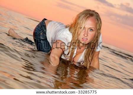 Sexy woman posing in the sea in wet clothes. - stock photo