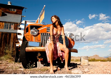 Sexy woman posing on a truck - stock photo