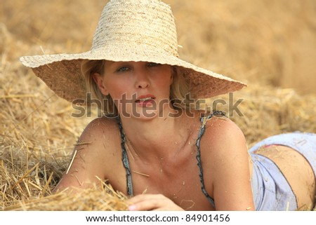 Sexy woman relaxing in hay stack on a summer day