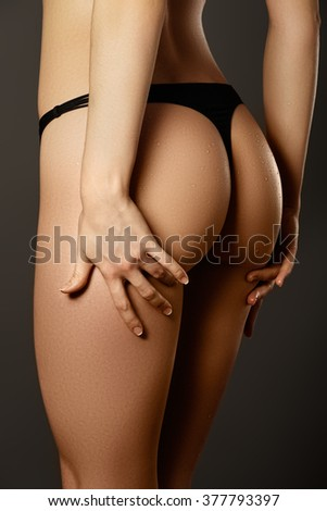 Sexy woman's sport buttocks in black lingerie close-up. Beautiful female body part. Sexy female buttocks isolated on white background. Beautiful female slim body.Beauty part of female body #377793397