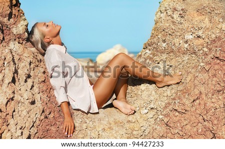 sexy woman sitting at beach enjoying the view of sea