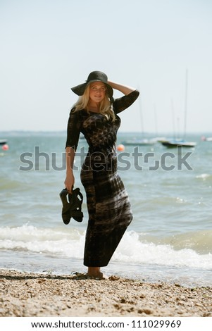 sexy woman standing in the water edge posing for the camera on a hot sunny day