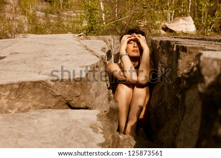 Sexy woman trapped in stones