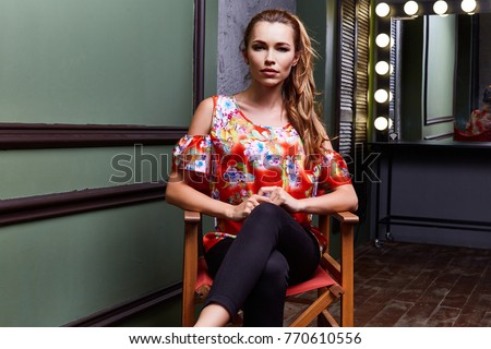 Sexy woman wear fashion clothes color blouse black pants seat on chair director actress actor film maker dressing room mirror lamp light model pose glamor makeup interior studio blond hair beautiful.