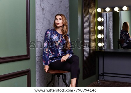 Sexy woman wear fashion clothes color blouse black pants seat on chair director actress actor film maker dressing room mirror lamp light model pose glamor makeup interior studio blond hair beautiful. #790994146