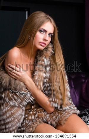 sexy woman wearing a fur coat posing