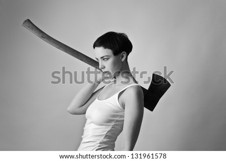 sexy woman wearing a vest top and bikini bottoms looking mean holding a axe