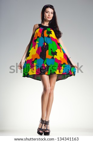 sexy woman wearing colorful summer dress on light grey background