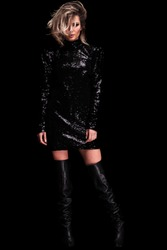 sexy woman wearing shiny black dress and long leather boots standing on black background, having a messy blonde hair, full body picture