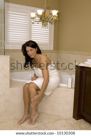 sexy woman wearing towel touching her legs in bathroom