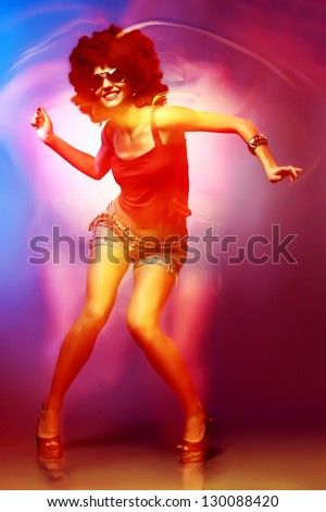 Sexy woman with afro haircut is dancing disco. Disco 80 style.