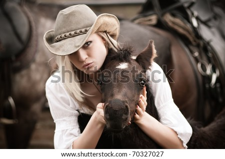Sexy woman with cowboy hat hugs a foal