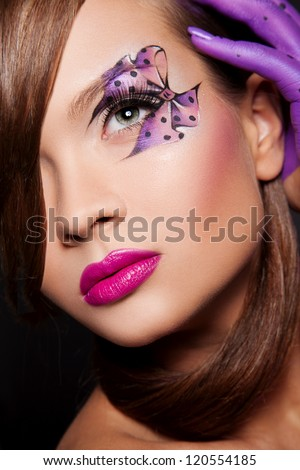 sexy woman with creative makeup and body art elements in violet color