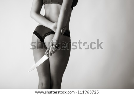 sexy woman with her back to camera in underwear hands down by her side in one hand she is holding a knife