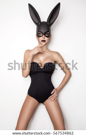 Stock Photo Sexy woman with large breasts wearing a black mask Easter bunny standing on a white background and looks very sensually