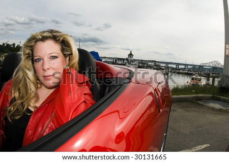 sexy woman with red sports car by a yacht club on the hudson river new york