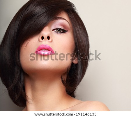 Sexy woman with straight black short hair and pink lips. Closeup