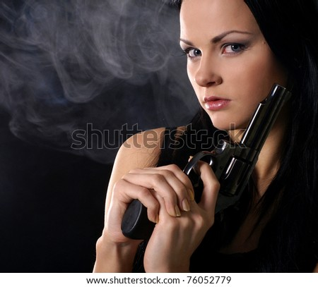 Sexy woman with weapon on a smoky background