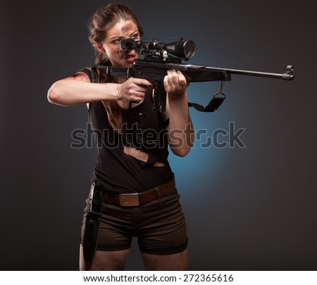 Sexy woman with weapon on dark background. Riot girl.