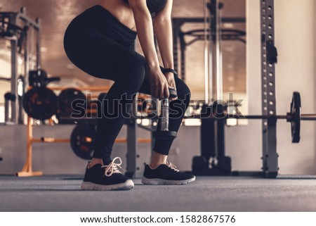 Sexy women lifting dumbbells workouts with dumbbells in a gym. Sport women at fitness.