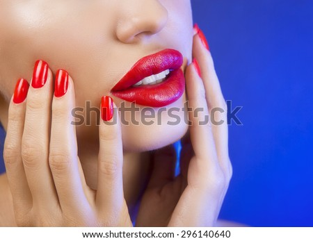 Sexy Young Beautiful Girl with Red Lips and Red Nail Polish, Bright Glistening  Shining Make-up Closeup on blue Background