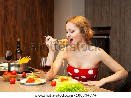 Sexy young blond woman eating spaghetti in the kitchen at home