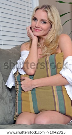 Sexy young blonde woman sitting on couch wearing only a men's shirt - coy expression - covering torso with pillow