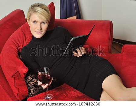 Sexy young blonde woman wearing a black dress holding a glass of red wine and reading an e-reader on a red couch