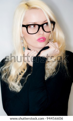 Sexy young blonde woman wearing glasses in black