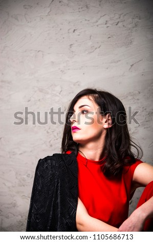 Sexy young brunette is sitting in a red club-chair. Studio, isolated on grey rustic background. #1105686713