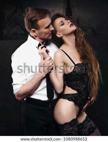 Sexy young brunette woman with fit slim body and long curly hairstyle seduce old handsome rich business man. She wears lace lingerie, he is in white shirt and tie. Dark dim light. Grunge background