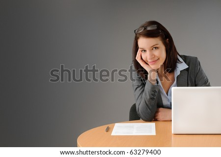 Sexy young businesswoman sitting at her desk smiling