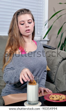 Sexy young Caucasian woman sitting in living room dipping chocolate chip cookies in milk - snack - stock photo