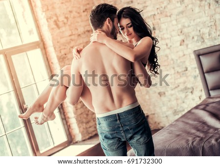 Sexy young couple at home. Handsome topless man is holding smiling woman in his arms #691732300