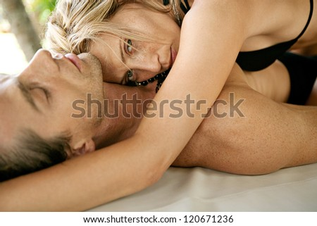 Sexy young couple hugging and being affectionate while lounging together on a tropical garden bed while on vacations in an exotic destination.