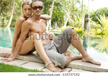 Sexy young couple hugging while lounging on the edge of an exotic swimming pool in a tropical hotel destination, outdoors.