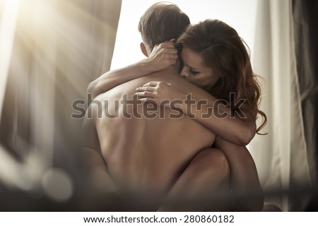 Sexy young couple kissing and playing in bed.
