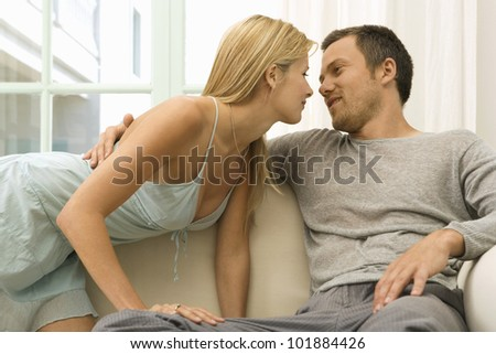 Sexy young couple kissing on home's sofa, being romantic and smiling.