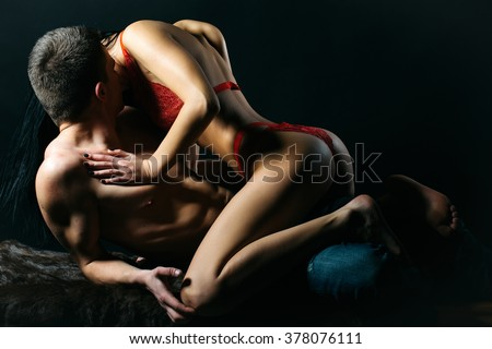 Sexy young couple of undressed sensual woman with straight body in red lace erotic lingerie sitting above muscular man kissing posing indoor on dark background, horizontal picture